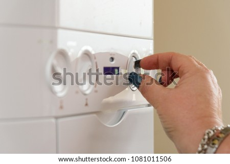 Woman with long nails turning the controls of a British Combi Gas Boiler