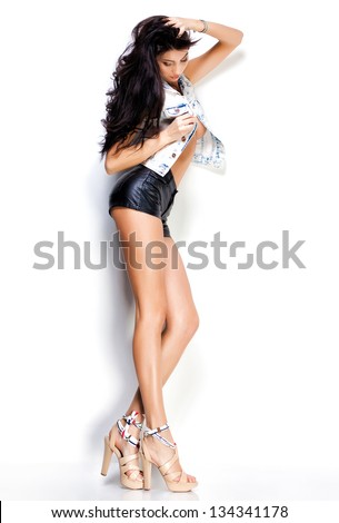 woman with long sexy legs wearing leather shorts and denim jacket on white background