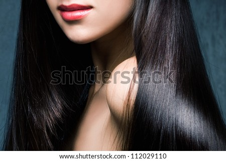 woman with long shiny black hair and red lips studio shot