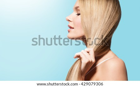 Stock Photo Woman with long thick straight hair in sun on a blue background in profile