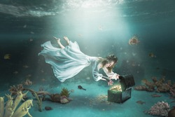Woman with long white dress swims underwater in the ocean and discovers a treasure chest full of gold coins. Adventure, wealth and success concept.