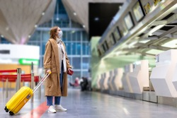 Woman with luggage stands at almost empty check-in counters at the airport terminal due to coronavirus pandemic/Covid-19 outbreak travel restrictions. Flight cancellation.Quarantine all over the world
