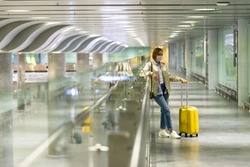 Woman with luggage stuck at empty airport terminal due to coronavirus pandemic/Covid-19 outbreak travel restrictions. Flight cancellation. Travel industry financial crisis.Quarantine isolation measure