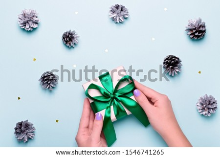 Woman with manicure holding green gift box or wrapped present on blue background with painted silver pine cones and golden confetti. Christmas presents or shopping concept. Top view