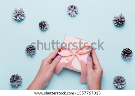 Woman with manicure holding green gift box or wrapped present on blue background with painted silver pine cones and golden confetti. Christmas presents or boxing day shopping concept. Top view