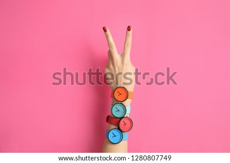 Woman with many bright wrist watches on color background, closeup. Fashion accessory Сток-фото ©