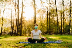 Woman with mask meditating in nature alone.Social distancing and active healthy lifestyle. Mindfulness meditation practice.Breathing exercise.Lotus yoga pose.Positive energy,optimism.