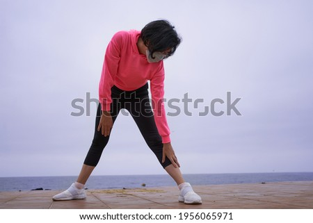 Woman with mask performs leg stretches before exercising with her back to the sea. New normal. sport session Foto stock ©