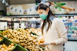 Woman with mask safely shopping for groceries amid the coronavirus pandemic in a stocked grocery store.COVID-19 food buying in supermarket.Panic buying,stockpiling.Shortage of fresh produce,vegetables