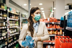 Woman with mask safely shopping for groceries amid the coronavirus pandemic in a stocked grocery store.COVID-19 food buying in supermarket.Panic buying,stockpiling.Lockdown preparation.Water shortage
