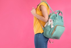 Woman with maternity backpack for baby accessories on color background, closeup. Space for text
