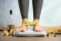 Woman with measuring tape using scale surrounded by food and alcohol after party on floor. Overweight problem