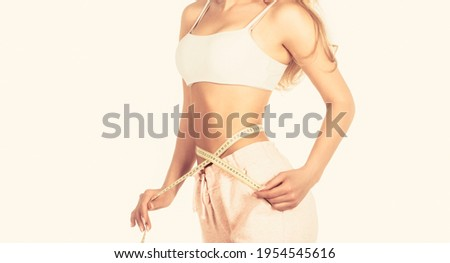 Woman with measuring tape. Weight loss concept. Woman take waist scale tape show her thin waist. Slim girl with centimeter. Closeup woman measuring her waist with tape. Slim woman's body. Photo stock ©