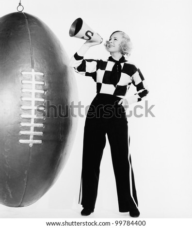Woman with megaphone and huge football - stock photo