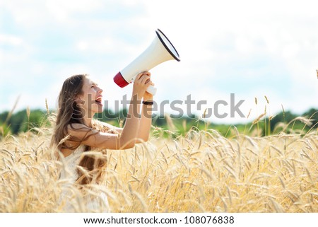 Woman with megaphone in the wheat field - stock photo