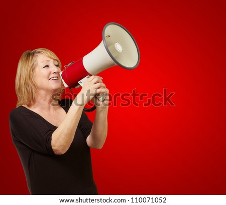 Woman with megaphone isolated on red background