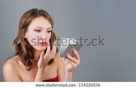 Woman with mirror.Beautiful young woman having make-up and looking in the mirror. Studio shot. Empty space for text. Gray background.