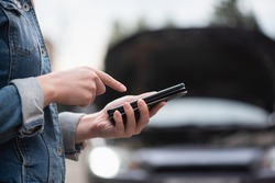 Woman with mobile phone on the broken car background. Tow truck service. Car service call.