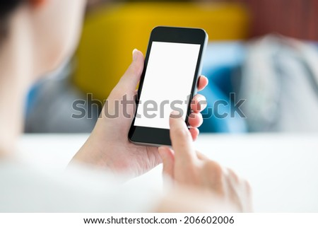 Woman with modern mobile phone in hands touching on a blank screen. Blurred office interior on a background.