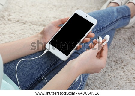 Woman with modern phone and earphones sitting on floor. Concept of audiobook #649050916