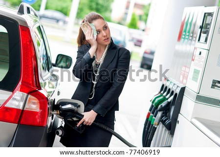 woman with money in her hand refuel car in gas station