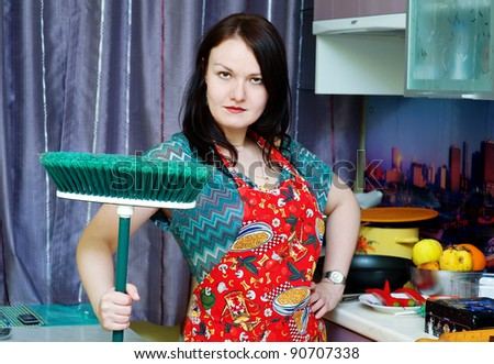 Woman with mop on the kitchen