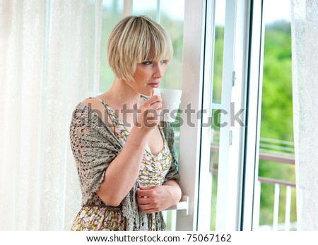 woman with morning coffee looking through window