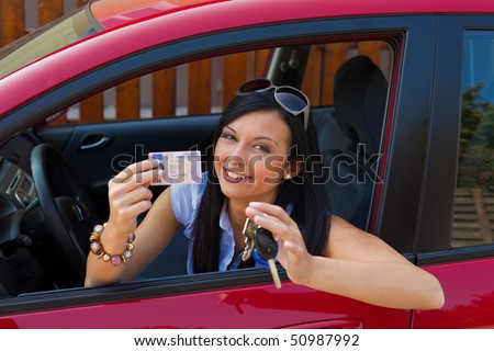 Woman with new car and driveru0026#39;s license and car keys