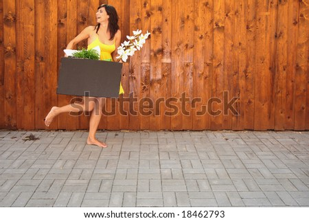 Woman with packed cardboard box going at the wall with flower