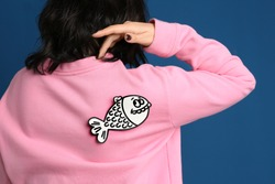 Woman with paper fish on back against blue background, closeup. April fool's day