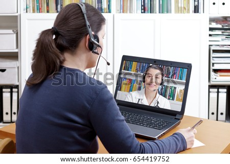 Woman with pen and paper and a headset in front of her computer making a video call with her doctor,  e-health, telehealth or telemedicine concept