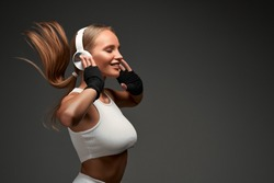 Woman with perfect abs wearing headphones and white clothes standing in gym isolated grey background. Copy space.