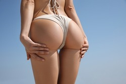 Woman with perfect body in bikini near sea, closeup. Back view