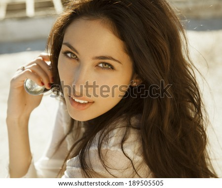 Woman with perfume. Smiling beautiful woman holding bottle of perfume and smelling aroma. horizontal shot