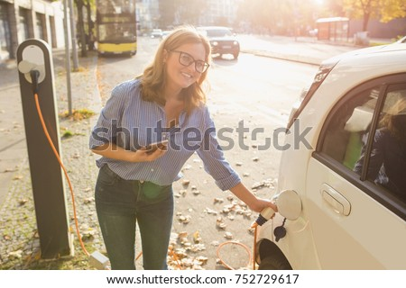 Woman with phone near an rental electric car. Vehicle charged at the charging station. #752729617