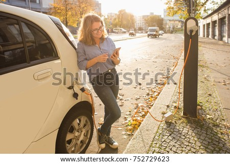 Woman with phone near an rental electric car. Vehicle charged at the charging station. #752729623