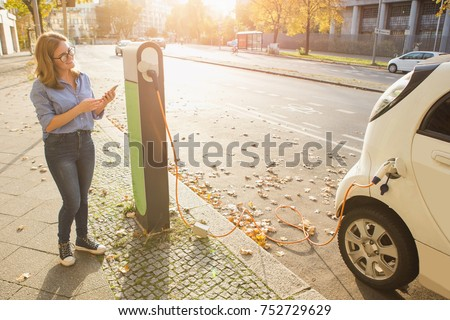 Woman with phone near an rental electric car. Vehicle charged at the charging station. #752729629