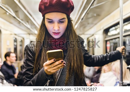 Woman with phone travelling by metro in Moscow. Beautiful young woman typing on the phone on her commute to work. Travel and lifestyle concepts