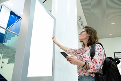 Woman with phone uses self-service desk with touch screen