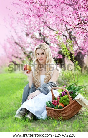 woman with picnic crib eating apple on the green grass