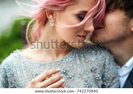 Woman with pink hair leans to her man tender