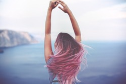 Woman with pink hair standing on the mountain top over blue sea view, photo toned