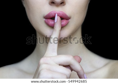 Woman with pink lipstick and finger showing hush silence sign, gesture and beauty concept,  black background.