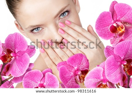 Woman with pink makeup. Fresh orchids on foreground
