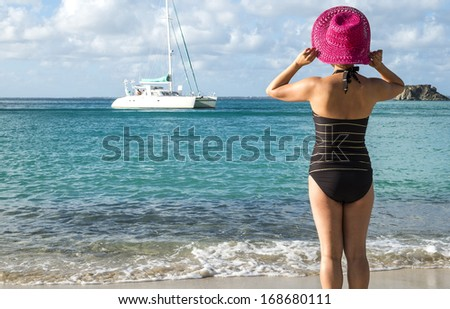 Woman with Pink Straw Hat Looking Out to the Caribbean Sea