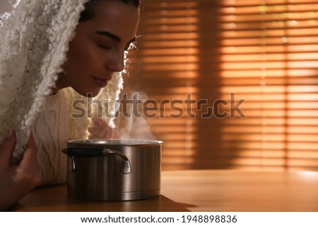 Woman with plaid doing inhalation above saucepot at table indoors. Space for text Stock photo ©