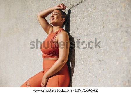 Woman with plus size body leaning to a wall and relaxing after workout session outdoors. Woman in sports clothing taking a break from exercise. Foto stock ©