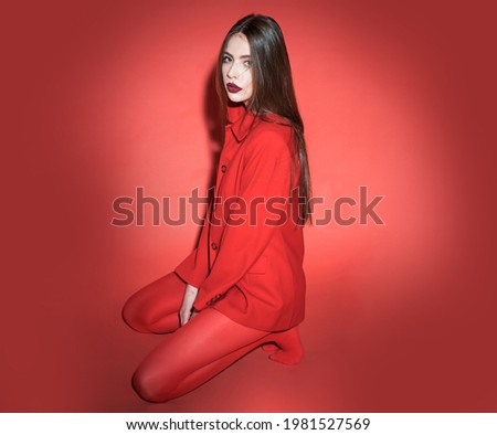 Woman with posing in total red outfit. Fashion concept. Girl on calm face in red formal jacket and tights, red background. Lady looking at camera while sitting on floor. Stock photo ©