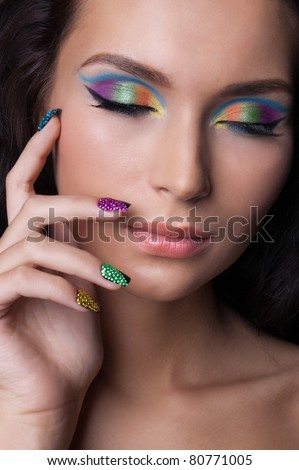 Woman with professional colourful make-up and sparkling manicure