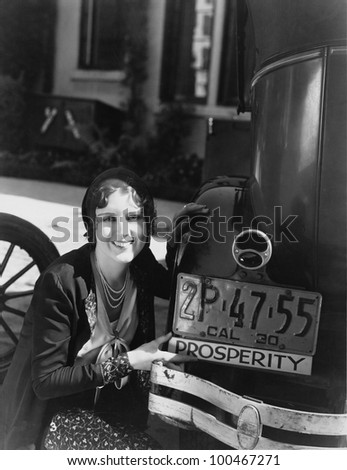 Woman with prosperity sign on car bumper